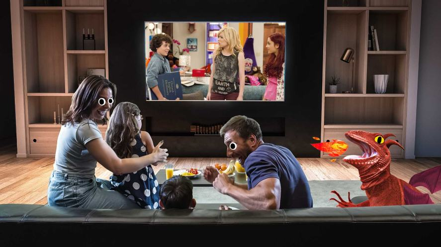 A family and a dragon watching TV