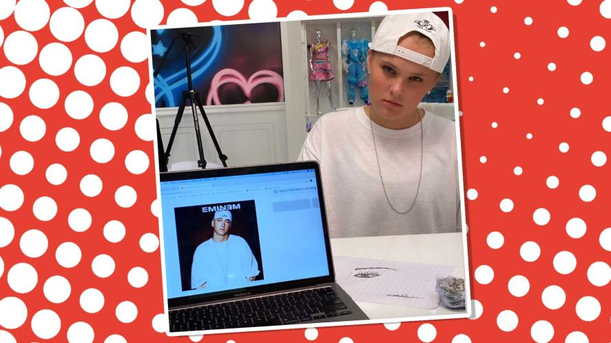 JoJo Siwa standing in front of a laptop which shows a picture of the rapper Eminem
