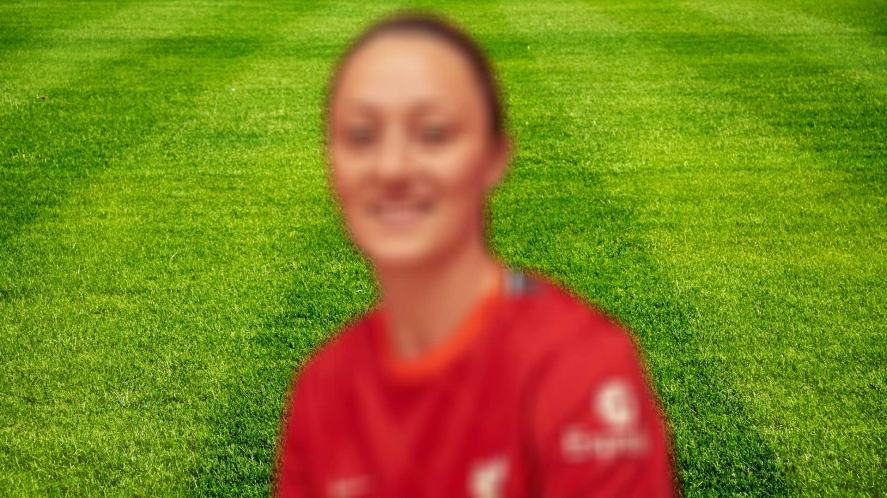 A blurred image of a footballer in a red shirt