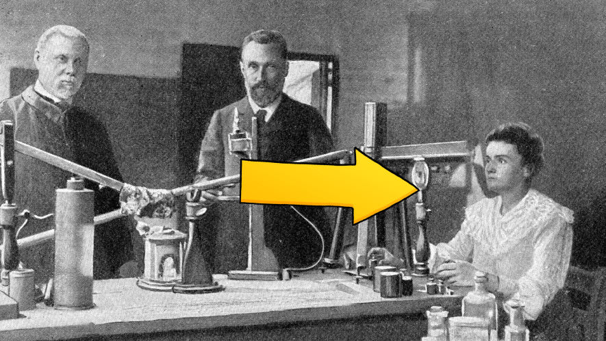 Old picture of three people, with yellow arrow pointing to Marie Curie