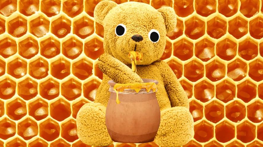 A toy bear eating honey