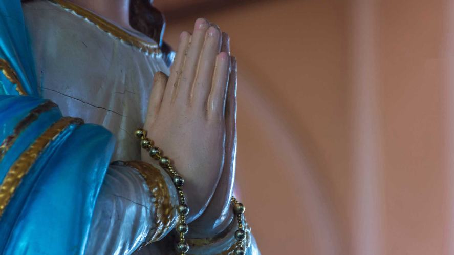 A religious statue with hands praying