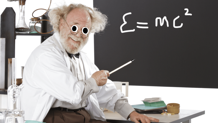 Mad professor type man pointing to blackboard and surrounded by science equipment