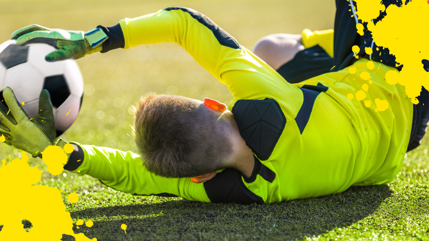 Goalkeeper diving for ball with yellow splats