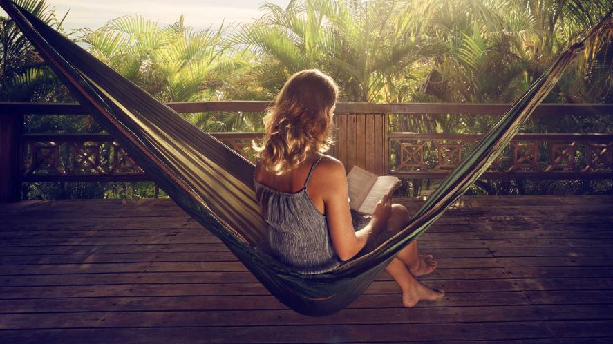 A girl reading a book in a hammock