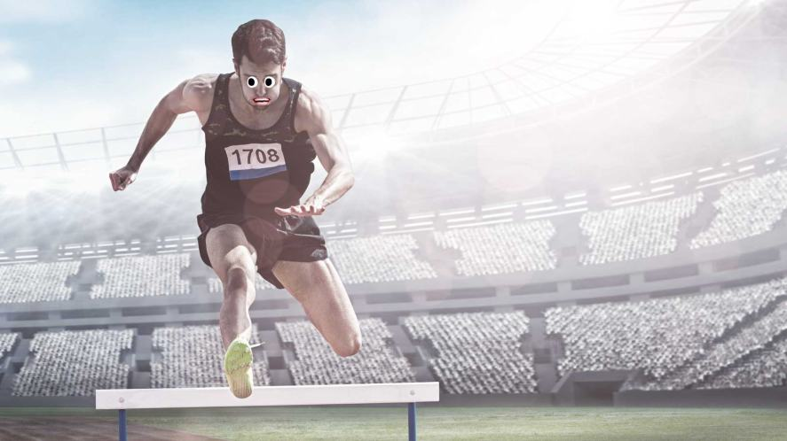 A male athlete jumping over a hurdle