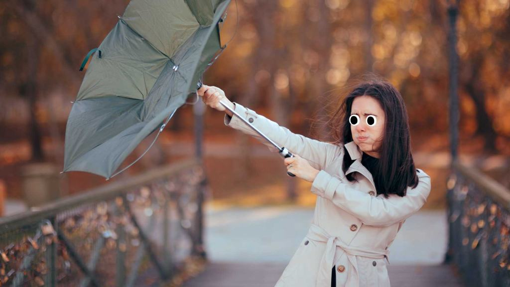 A person struggles to hold an umbrella up during a windy day