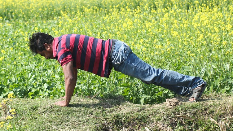 A man exercising in a field