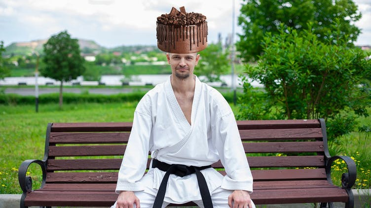 A man in a karate suit with a chocolate cake on their head