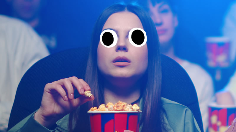 A woman eating popcorn at the cinema
