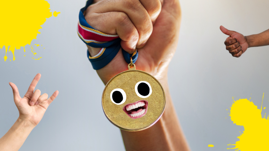 A hand clutching a gold medal