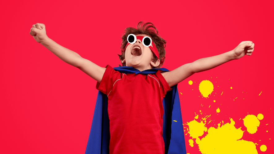 Boy dressed as superhero on red background