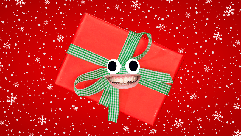 Smiling red Christmas present with a green ribbon wrapped around it
