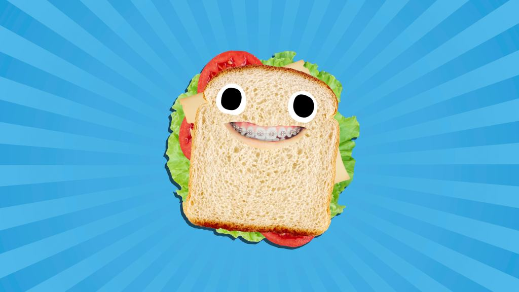 A grinning sandwich with cheese, tomato and lettuce inside