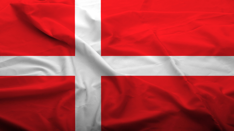 A flag. An off centre white cross on a red background.