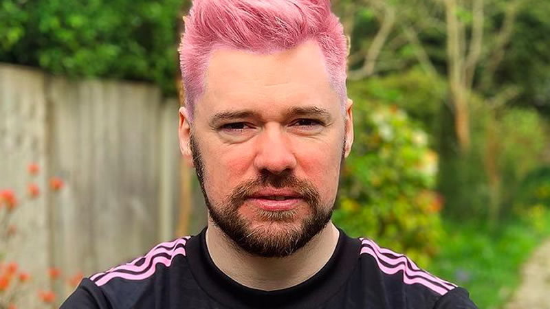 Famous YouTuber looks down the camera lens. He has pink hair and is standing by a tatty wooden fence