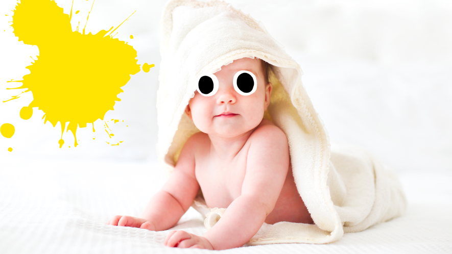 Baby on bed with yellow splat