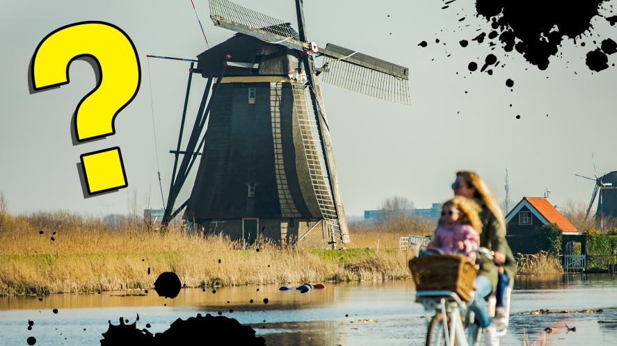 Some Dutch people cycle past a windmill