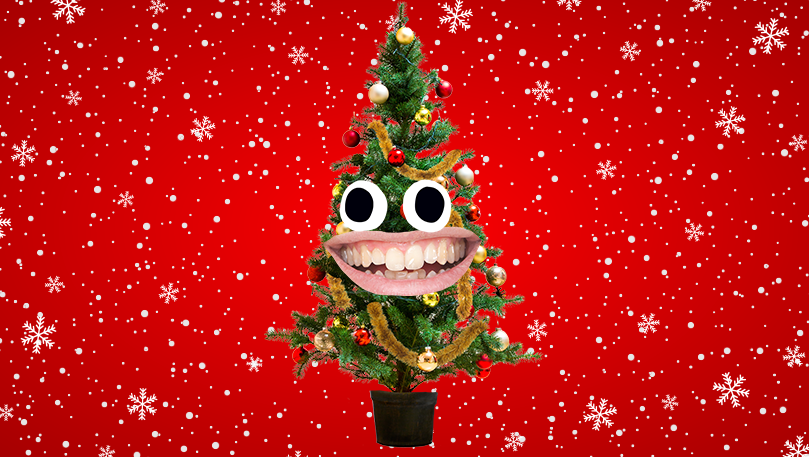 A laughing Christmas tree in front of a Christmas themed red background