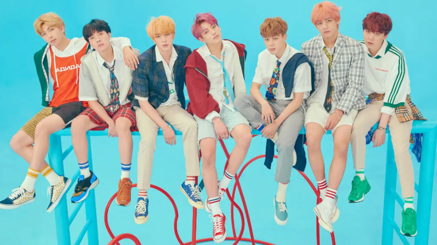BTS sitting on some kind of climbing frame