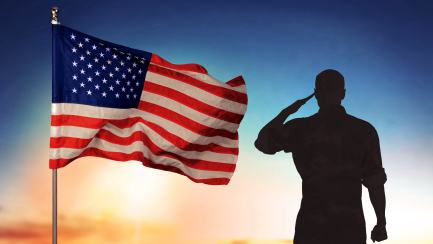 A person saluting next to the USA flag