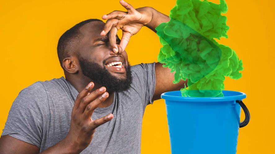 A man holding his nose over a bucket