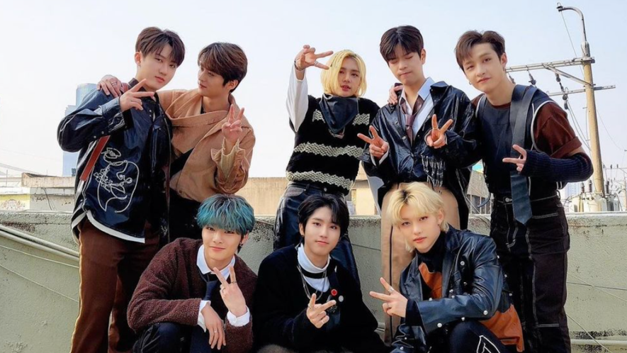 Stray Kids posing for a photo on a roof