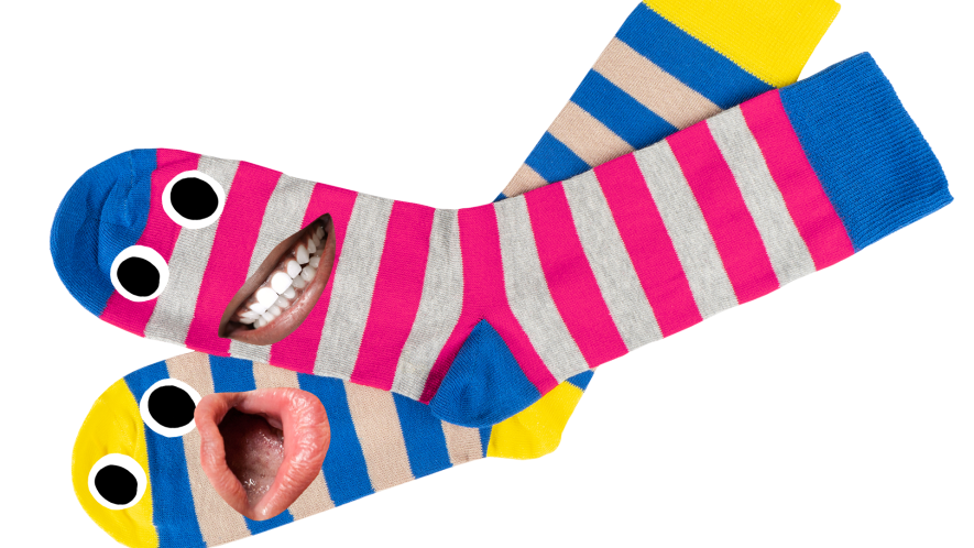 Pair of mismatched stripy socks on white background with silly faces