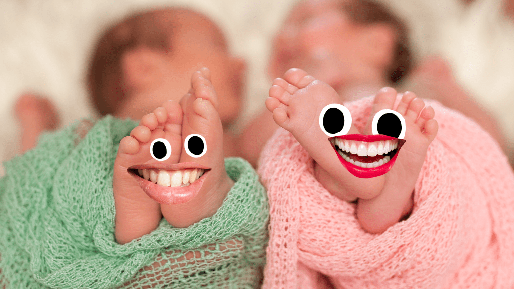Two babies feet with smiley faces on them