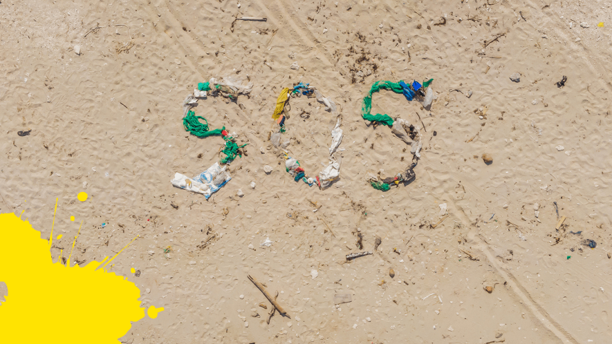 Beach with SOS spelled out with debris