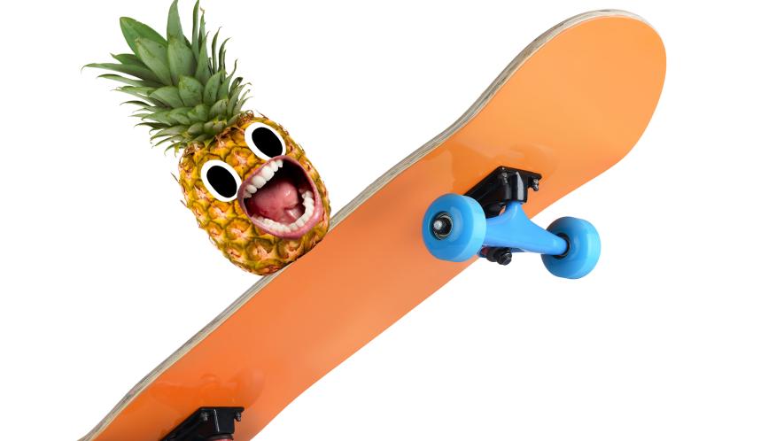 Screaming pineapple on skateboard on white background