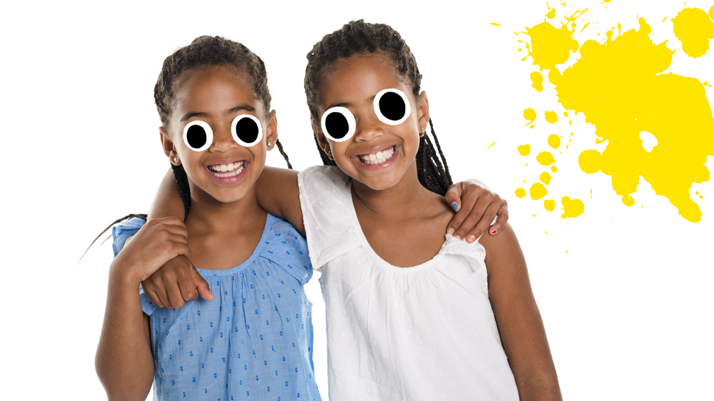 Smiling female twins with yellow splat