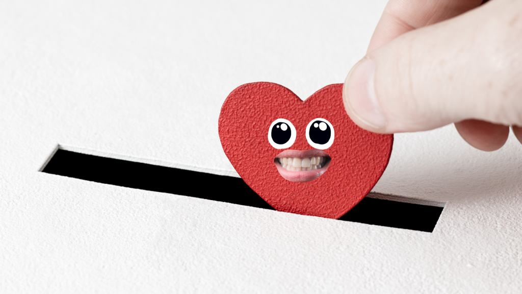 A heart shaped piece of card being dropped into a piggy bank slot