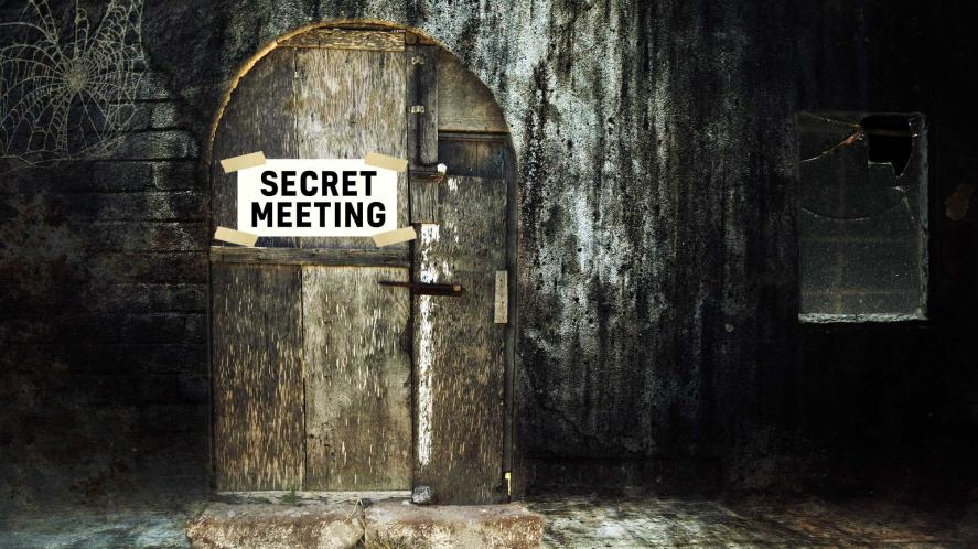 A door with a note saying Secret Meeting