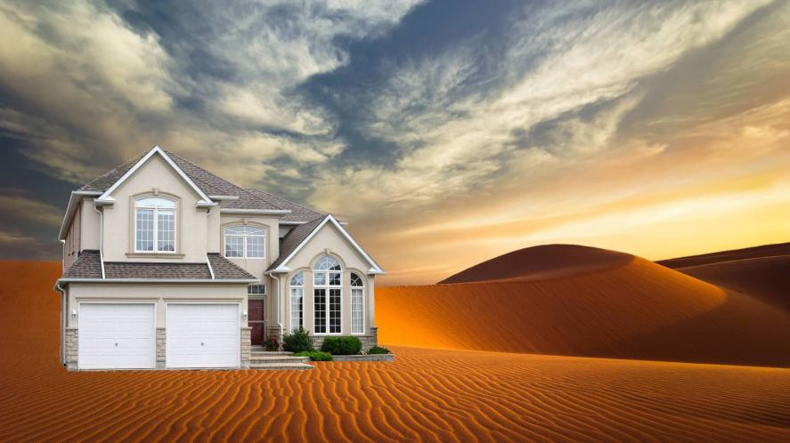 A house plonked in the middle of a very sandy desert
