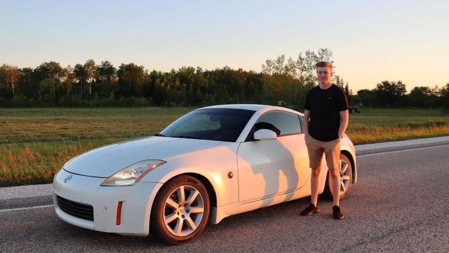 Luke standing next to a sports car