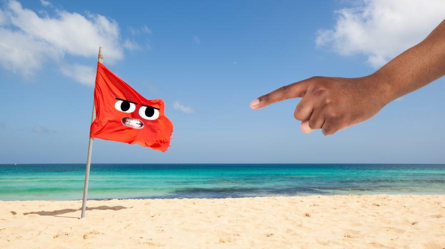 A red flag on a sandy beach