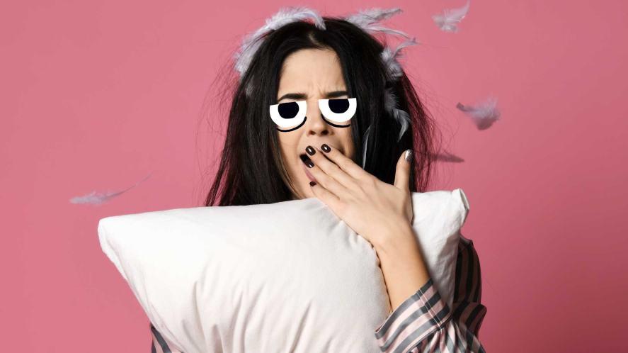 A sleepy woman holding a feather pillow