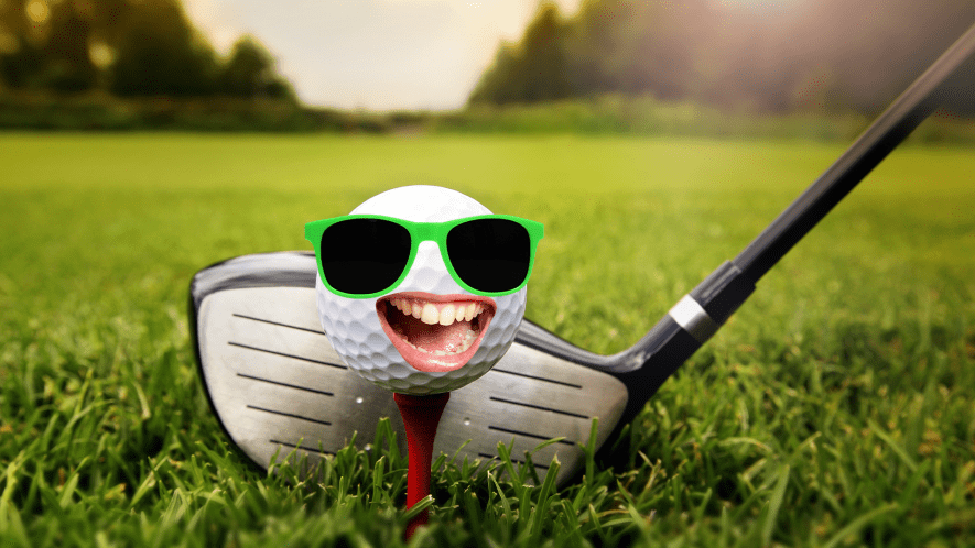Golf ball with goofy face and club on grass