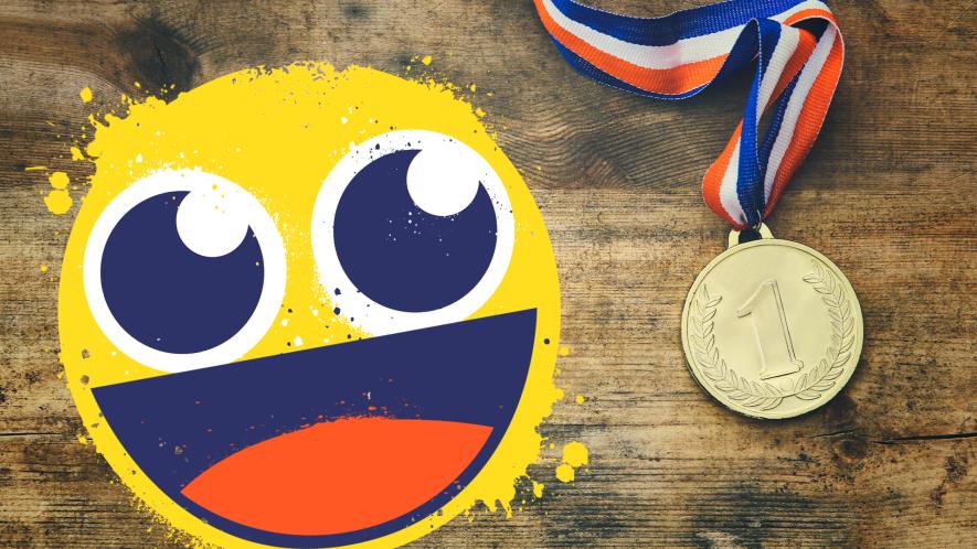 Smiling emoji with gold medal on wooden background