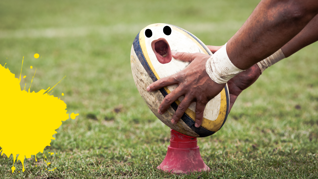 Hands placing rugby ball with face on grass with yellow splat