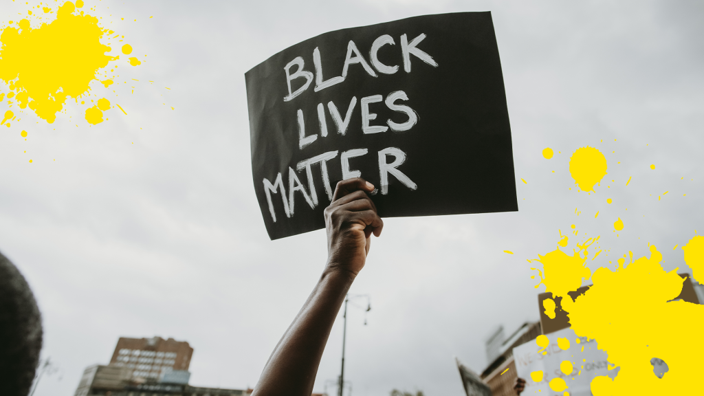 Hand holding a Black Lives Matter sign with yellow splats