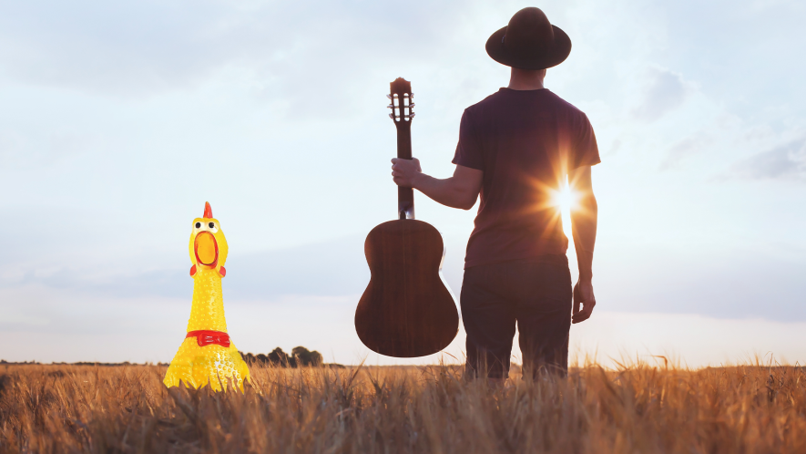 Man with guitar and cowboy hat in a field, with rubber chicken peeking out from the grass