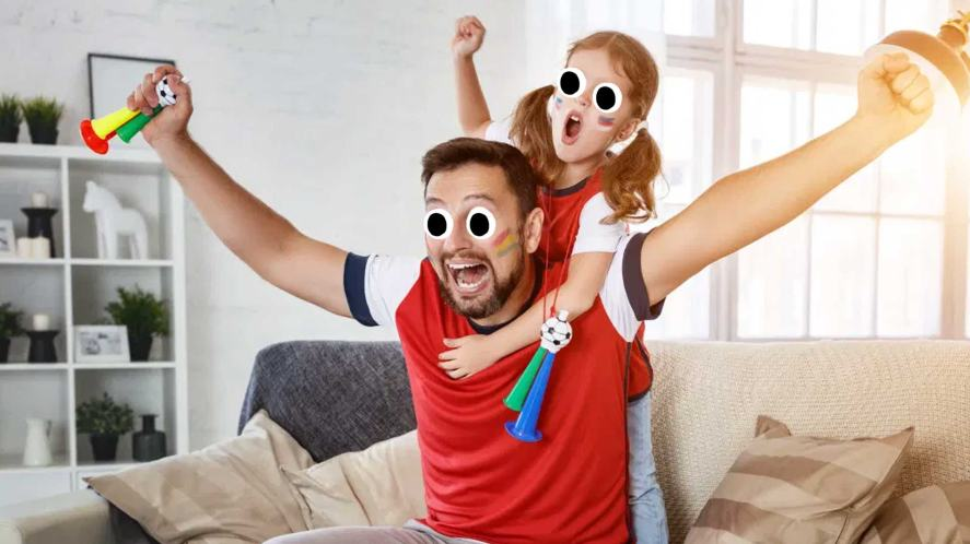 A dad and daughter watching the football on telly