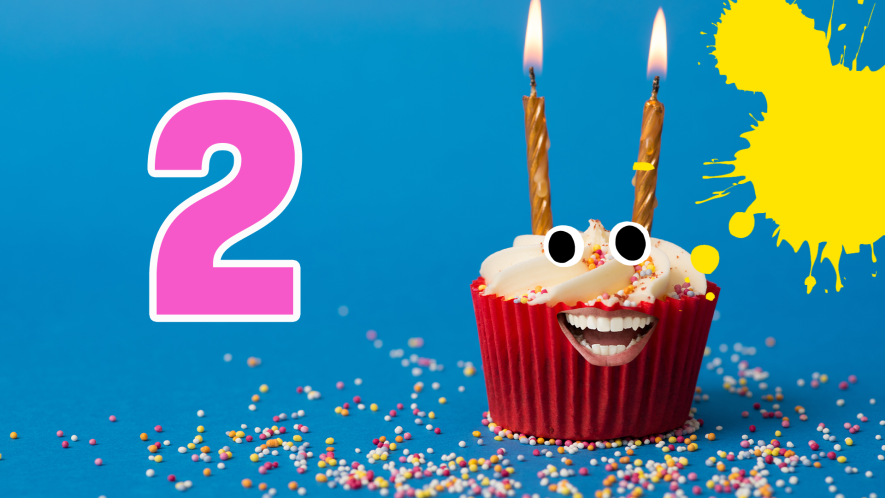 Cake with two candles and face, the number 2 and splats on blue background with sprinkles
