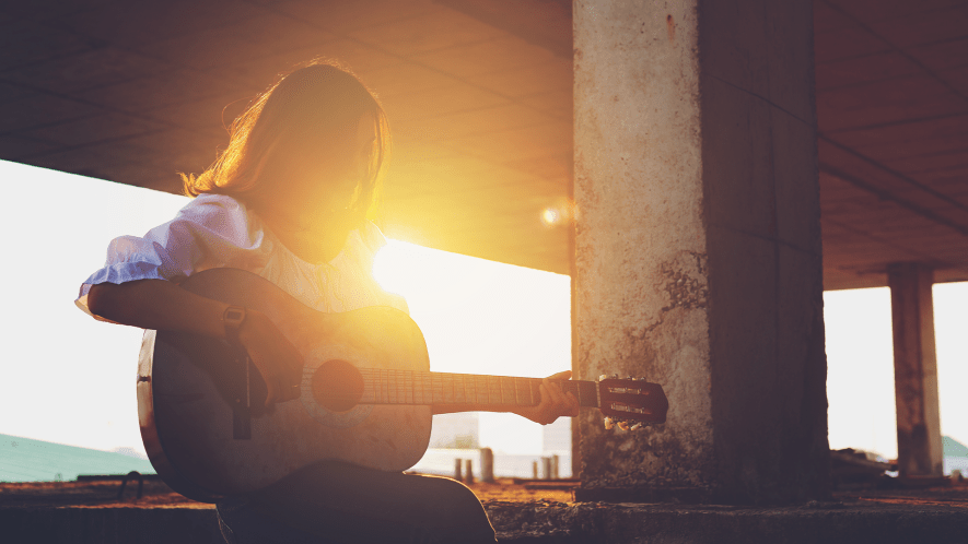 Girl with guitar in sunset