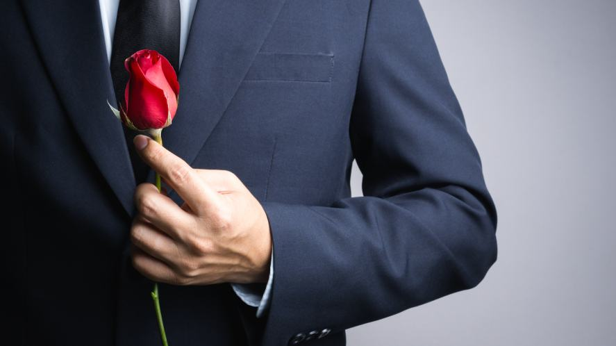 A politician holding a red rose to represent Labour