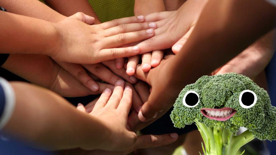 A team joining hands, while a piece of broccoli looks on
