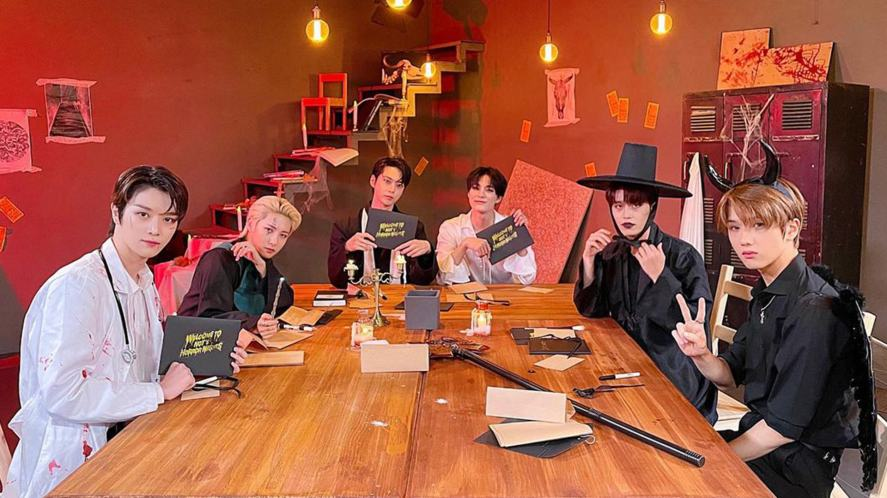 The members of NCT sitting around a table