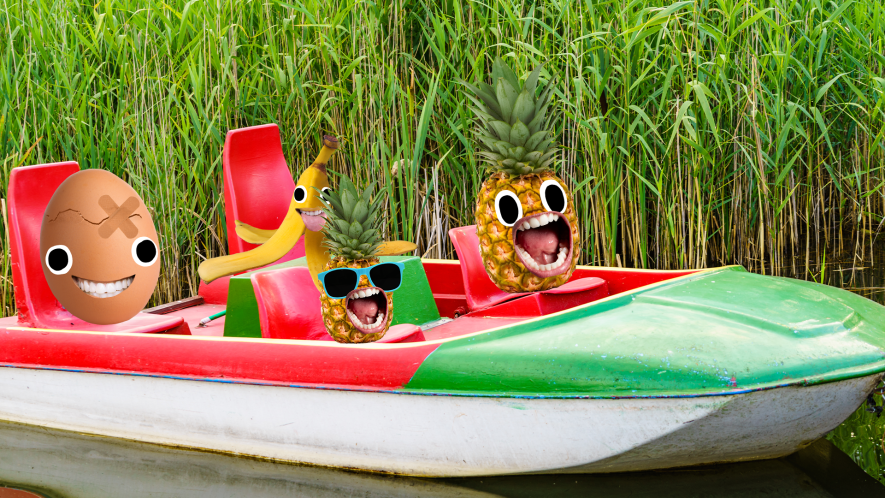 Two pineapples, a banana and an egg in a small pedalo